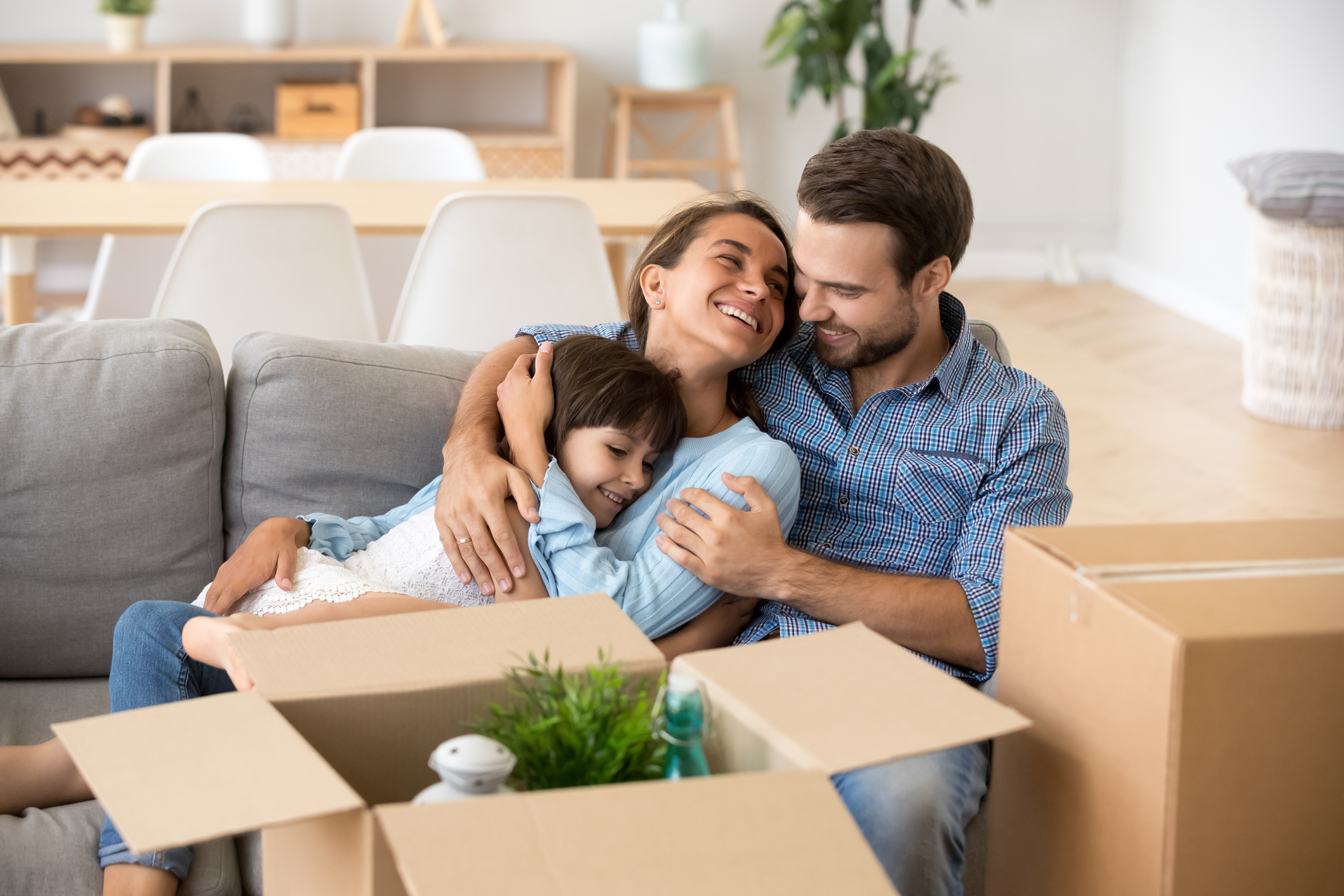 Happy mom dad with kid daughter embracing smiling relaxing on couch after relocation moving to Tampa in new home concept, young parents hugging child girl sitting on sofa unpacking boxes, family moving day